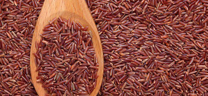 Riso rosso sparso e su un cucchiaio di legno